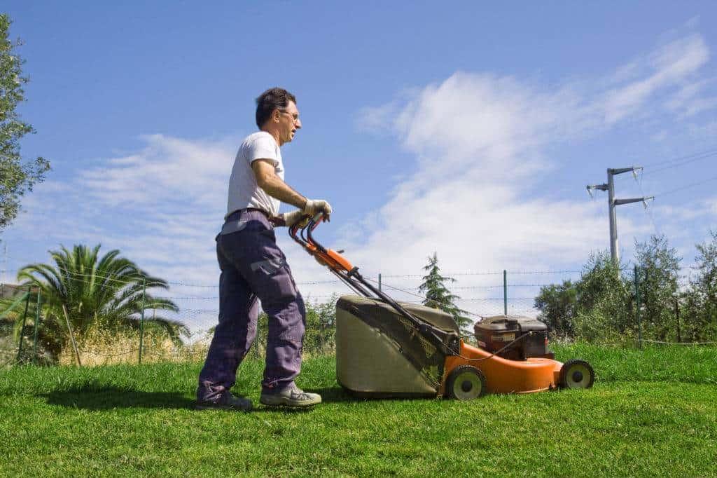maintenance worker mowing school grounds lawn